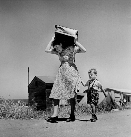 Robert Capa koman carrying luggage small boy, Haifa